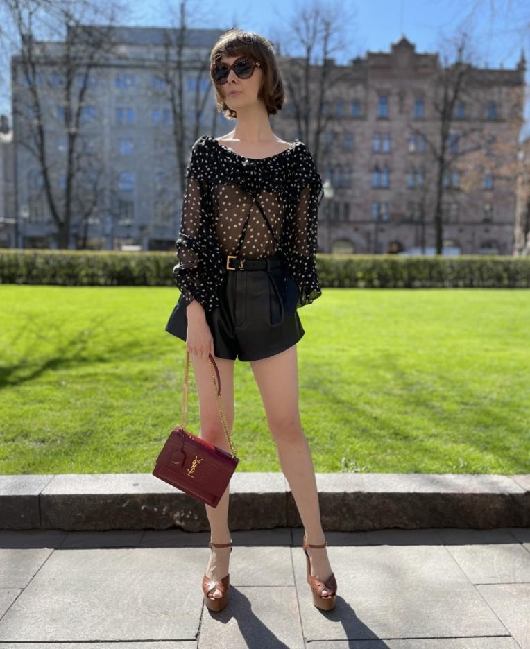 Kadulla seisovalla naisellayllään Saint Laurent sifonkipaita, nahkashortsit ja kädessä YSL laukku, jalassa Celinen avokkaat.