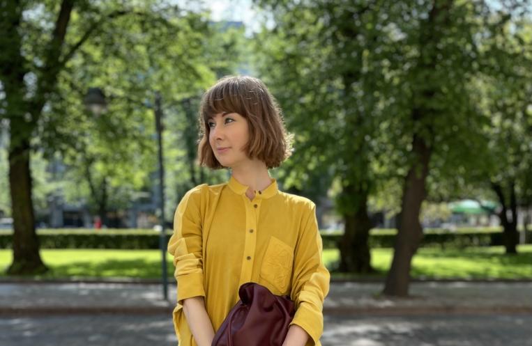 nainen seisoo puistossa keltainen mekko yllään ja käsilaukku kädessään.