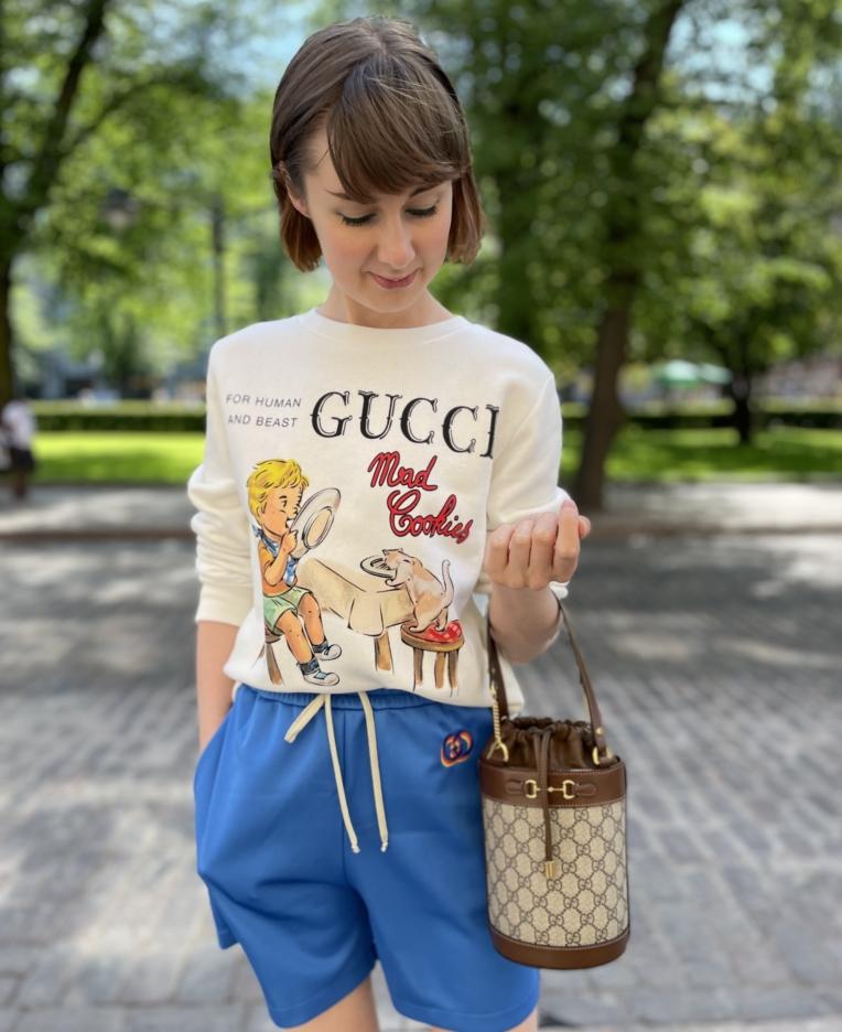 Naisella yllään Guccin college, shortsit ja käsivarrellaan laukku.