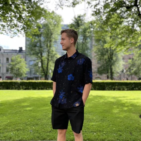 Mies seisoo puistossa yllään t-paita ja shortsit.